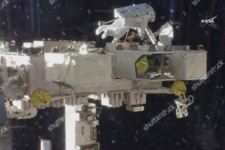 Stock Image of In this image from video made available by NASA, astronaut Drew Feustel prepares to close a door to an atmospheric experiment during a space walk outside the International Space Station on