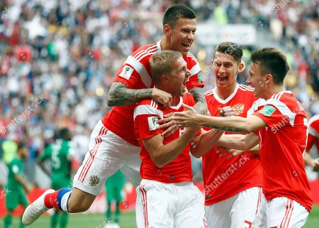 Russia's Yuri Gazinsky celebrates with teammates after scoring his side's first goal during the group A match between Russia and Saudi Arabia which opens the 2018 soccer World Cup at the Luzhniki stadium in Moscow, Russia