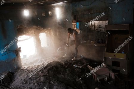 """Angelica Maria Alvarez rests, exhausted inside her home destroyed by the eruption of the the Volcan de Fuego or """"Volcano of Fire,"""" in San Miguel Los Lotes, Guatemala, . Alvarez is still searching for the remains of more than 10 members of her family, including her husband and two daughters"""