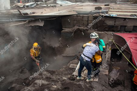 """A rescue worker comforts Angelica Maria Alvarez at the site of her home during the search for the remains of more than 10 of her family members, including her husband and two daughters, killed by the eruption of the Volcan de Fuego, or """"Volcano of Fire,"""" in San Miguel Los Lotes, Guatemala, . At least 110 people were killed when the volcano erupted June 3, sending waves of super-heated debris down onto villages on its flanks. About 200 people are listed as missing and authorities continue working to identify some of the recovered bodies"""