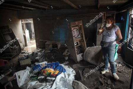 """Angelica Maria Alvarez talks on a cell phone from inside her home destroyed by the eruption of the Volcan de Fuego or """"Volcano of Fire"""", in San Miguel Los Lotes, Guatemala, . Alvarez is still searching for the remains of more than 10 family members, including her husband and two daughters"""