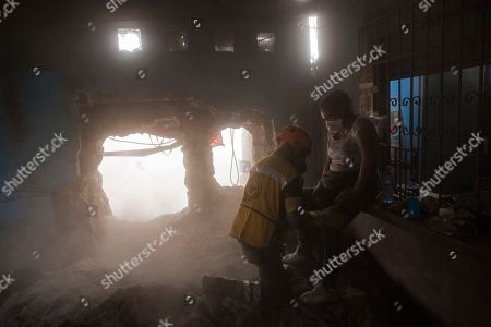 """Angelica Maria Alvarez is confronted by a Mexican search and rescue worker inside her home destroyed by the eruption of the Volcan de Fuego, or """"Volcano of Fire,"""" in San Miguel Los Lotes, Guatemala, . Alvarez is still searching for the remains of more than 10 family members, including her husband and two daughters"""