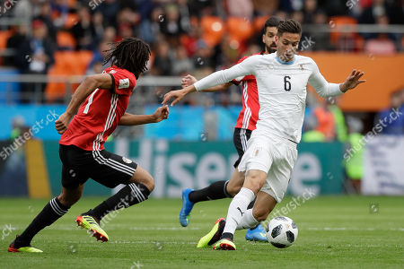 Uruguay's Rodrigo Bentancur, right, and Egypt's Kahraba, left, challenge for the ball during the group A match between Egypt and Uruguay at the 2018 soccer World Cup in the Yekaterinburg Arena in Yekaterinburg, Russia