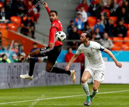 Kahraba (L) of Egypt and Diego Godin of Uruguay in action during the FIFA World Cup 2018 group A preliminary round soccer match between Egypt and Uruguay in Ekaterinburg, Russia, 15 June 2018.