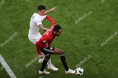 Jose Gimenez  of Uruguay in action against Mahmoud Kahraba (R) of Egypt during the FIFA World Cup 2018 group A preliminary round soccer match between Egypt and Uruguay in Ekaterinburg, Russia, 15 June 2018.