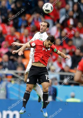 Egypt's Mahmoud Hamdy, foreground, jumps for the ball with Uruguay's Diego Godin during the group A match between Egypt and Uruguay at the 2018 soccer World Cup in the Yekaterinburg Arena in Yekaterinburg, Russia