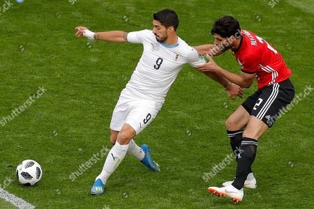 Egypt's Ali Gabr, right, holds Uruguay's Luis Suarez as they vie for the ball during the group A match between Egypt and Uruguay at the 2018 soccer World Cup in the Yekaterinburg Arena in Yekaterinburg, Russia