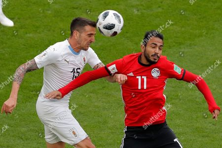 Egypt's Kahraba, right, jumps for the ball with Uruguay's Matias Vecino during the group A match between Egypt and Uruguay at the 2018 soccer World Cup in the Yekaterinburg Arena in Yekaterinburg, Russia
