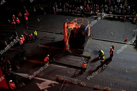 The lid is placed above artist Mike Parr as he is encased beneath Hobart's Macquarie St during Tasmania's Dark Mofo festival in Hobart, Australia, 14 June 2018 (issued 15 June 2018). The performance is called 'Underneath The Bitumen The Artist'.