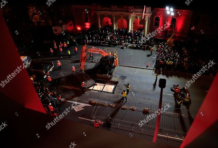 Crowds witness artist Mike Parr being encased beneath Hobart's Macquarie St during Tasmania's Dark Mofo festival in Hobart, Australia, 14 June 2018 (issued 15 June 2018). The performance is called 'Underneath The Bitumen The Artist'.