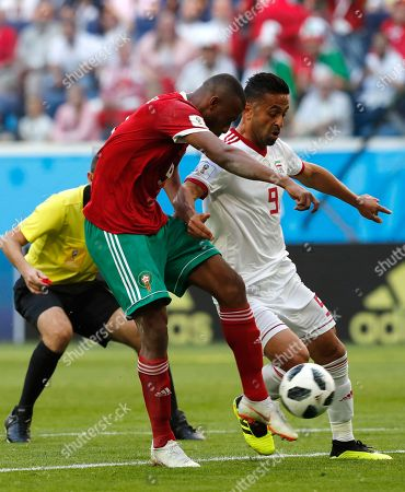 Ayoub El Kaabi (L) of Morocco and Omid Ebrahimi of Iran in action during the FIFA World Cup 2018 group B preliminary round soccer match between Morocco and Iran in St.Petersburg, Russia, 15 June 2018. (RESTRICTIONS APPLY: Editorial Use Only, not used in association with any commercial entity - Images must not be used in any form of alert service or push service of any kind including via mobile alert services, downloads to mobile devices or MMS messaging - Images must appear as still images and must not emulate match action video footage - No alteration is made to, and no text or image is superimposed over, any published image which: (a) intentionally obscures or removes a sponsor identification image; or (b) adds or overlays the commercial identification of any third party which is not officially associated with the FIFA World Cup)