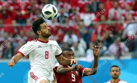 Morteza Pouraliganji of Iran and Ayoub El Kaabi of Morocco (R) in action during the FIFA World Cup 2018 group B preliminary round soccer match between Morocco and Iran in St.Petersburg, Russia, 15 June 2018. (RESTRICTIONS APPLY: Editorial Use Only, not used in association with any commercial entity - Images must not be used in any form of alert service or push service of any kind including via mobile alert services, downloads to mobile devices or MMS messaging - Images must appear as still images and must not emulate match action video footage - No alteration is made to, and no text or image is superimposed over, any published image which: (a) intentionally obscures or removes a sponsor identification image; or (b) adds or overlays the commercial identification of any third party which is not officially associated with the FIFA World Cup)