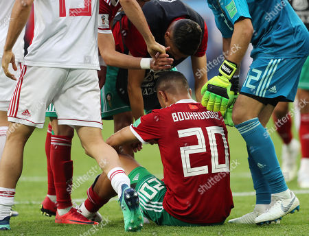 A dejected Aziz Bouhaddouz of Morocco sits down on the pitch at the end of the game