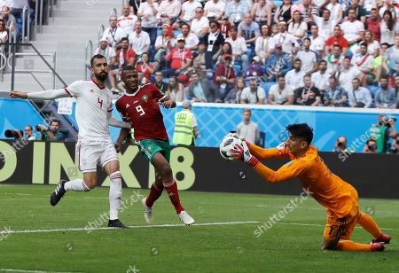 Iran goalkeeper Ali Beiranvand, right, stops the ball as Morocco's Ayoub El Kaabi, center, and Iran's Roozbeh Cheshmi, left, follow the ball during the group B match between Morocco and Iran at the 2018 soccer World Cup in the St. Petersburg Stadium in St. Petersburg, Russia