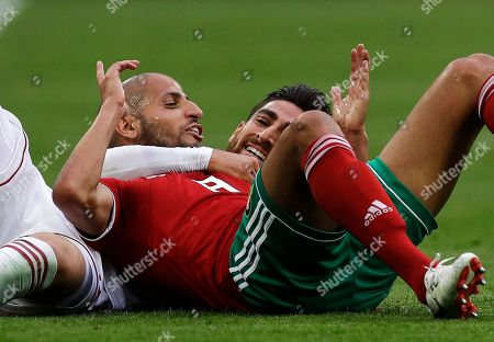 Morocco's Ayoub El Kaabi, front, and Iran's Alireza Jahanbakhsh, rear, smile after they collide to compete the ball during the group B match between Morocco and Iran at the 2018 soccer World Cup in the St. Petersburg Stadium in St. Petersburg, Russia