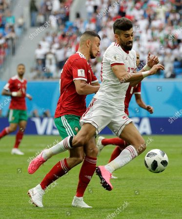 Iran's Ramin Rezaeian,right, is tackled by Morocco's Youssef Ait Bennasser during the group B match between Morocco and Iran at the 2018 soccer World Cup in the St. Petersburg Stadium in St. Petersburg, Russia