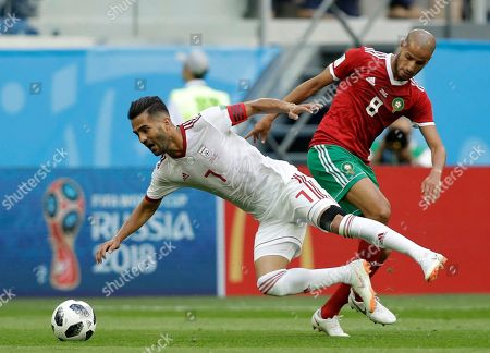 Iran's Masoud Shojaei, left, is tackled by Morocco's Karim El Ahmadi during the group B match between Morocco and Iran at the 2018 soccer World Cup in the St. Petersburg Stadium in St. Petersburg, Russia