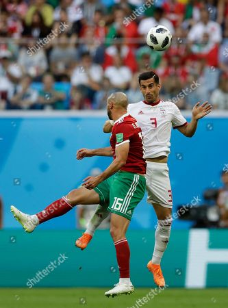 Morocco's Noureddine Amrabat, left, and Iran's Masoud Shojaei, vie for the ball, during the group B match between Morocco and Iran at the 2018 soccer World Cup in the St. Petersburg Stadium in St. Petersburg, Russia