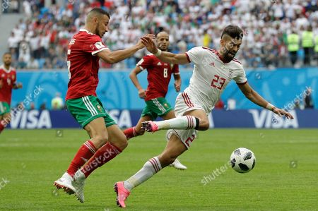 Iran's Ramin Rezaeian, right, is tackled by Morocco's Youssef Ait Bennasser during the group B match between Morocco and Iran at the 2018 soccer World Cup in the St. Petersburg Stadium in St. Petersburg, Russia