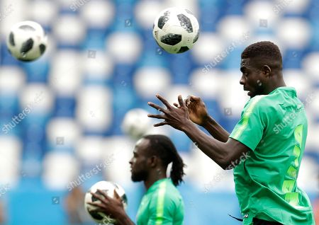 Stock Photo of Nigeria's John Ogu heads the ball during Nigeria's official training on the eve of the group D match between Croatia and Nigeria at the 2018 soccer World Cup in the Kaliningrad Stadium in Kaliningrad, Russia