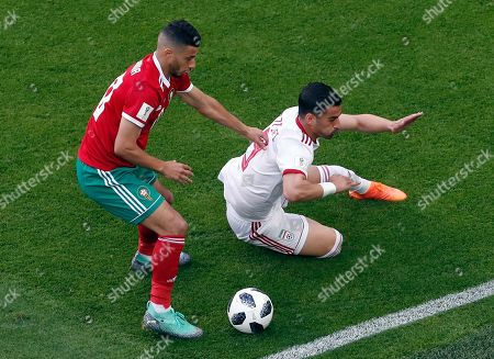 Morocco's Younes Belhanda, left, and Iran's Mehdi Torabi, right, challenge for the ball during the group B match between Morocco and Iran at the 2018 soccer World Cup in the St. Petersburg Stadium in St. Petersburg, Russia
