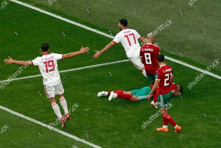 Players of iran celebrate as Morocco's Aziz Bouhaddouz lies on the pitch after scoring an own goal during the group B match between Morocco and Iran at the 2018 soccer World Cup in the St. Petersburg Stadium in St. Petersburg, Russia