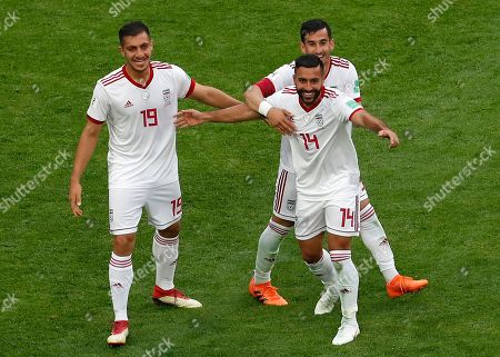 Iran's Majid Hosseini, left, and his teammates Saman Ghoddos, front, and Masoud Shojaei, rear, celebrate to win the group B match between Morocco and Iran at the 2018 soccer World Cup in the St. Petersburg Stadium in St. Petersburg, Russia