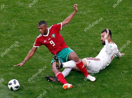 Morocco's Ayoub El Kaabi, left, and Iran's Roozbeh Cheshmi, right, challenge for the ball during the group B match between Morocco and Iran at the 2018 soccer World Cup in the St. Petersburg Stadium in St. Petersburg, Russia