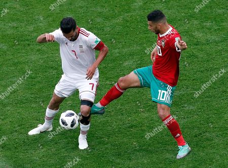 Iran's Masoud Shojaei, left, and Morocco's Younes Belhanda, right, challenge for the ball during the group B match between Morocco and Iran at the 2018 soccer World Cup in the St. Petersburg Stadium in St. Petersburg, Russia