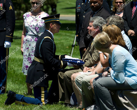 Stock Image of U.S. Army Capt. Christopher Blanchard presents the flag from the casket of Army Second Lt. Robert R. Keown to John F. Keown, during the burial at Arlington National Cemetery in Arlington, Va., on . Keown was piloting his P-38 aircraft when it crashed in Papua New Guinea in 1944