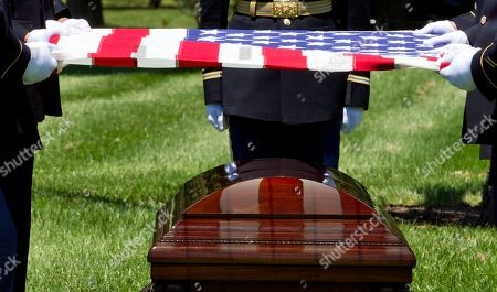 Stock Photo of An Army team holds a U.S. flag over the casket of U.S. Army Air Forces 2nd Lt. Robert R. Keown during a burial service at Arlington National Cemetery in Arlington, Va., on . Keown was piloting his P-38 aircraft when it crashed in Papua New Guinea in 1944