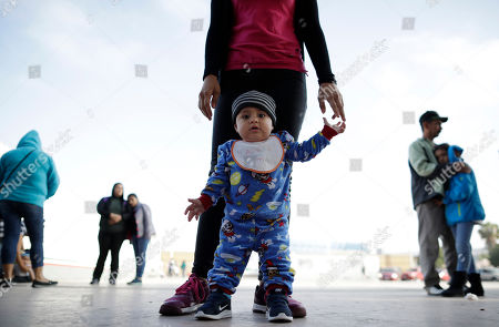 Nine month-old Jesus Alberto Lopez, center, stands with his mother, Perla Murillo, as they wait with other families to request political asylum in the United States, across the border in Tijuana, Mexico. The family, from the Mexican state of Michoacan, has waited for about a week in this Mexican border city, hoping for a chance to escape widespread drug violence at home