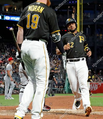 Pittsburgh Pirates' Elias Diaz (32) is greeted by Colin Moran (19) after scoring on a sacrifice fly by Starling Marte off Cincinnati Reds relief pitcher Michael Lorenzen in the sixth inning of a baseball game in Pittsburgh