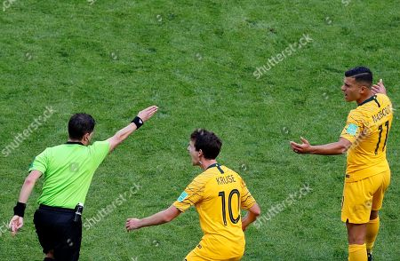 Australia's Robbie Kruse, center, and Andrew Nabbout, right, react on referee Andres Cunha from Uruguay, left, after he watches a replay on a screen during the group C match between France and Australia at the 2018 soccer World Cup in the Kazan Arena in Kazan, Russia