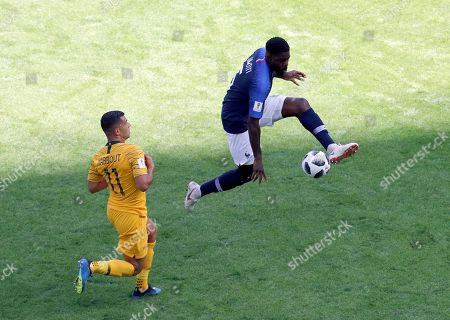 France's Samuel Umtiti, right, duels for the ball with Australia's Andrew Nabbout during the group C match between France and Australia at the 2018 soccer World Cup in the Kazan Arena in Kazan, Russia