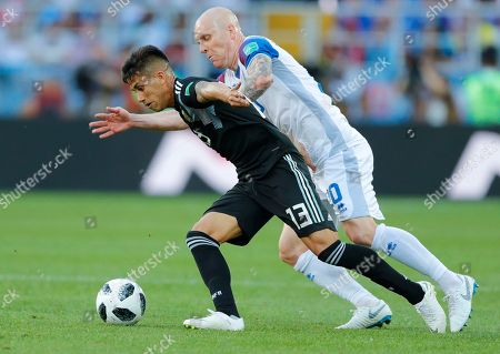 Argentina's Maximiliano Meza, left, challenges for the ball with Iceland's Emil Hallfredsson during the group D match between Argentina and Iceland at the 2018 soccer World Cup in the Spartak Stadium in Moscow, Russia