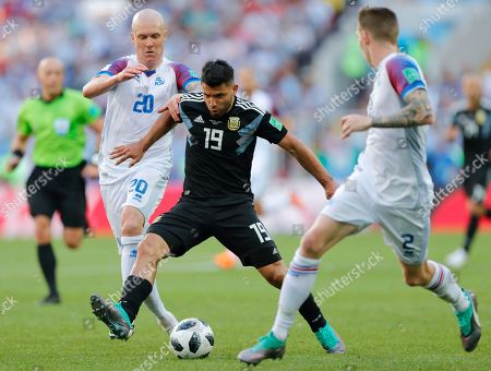 Iceland's Emil Hallfredsson, left, challenges for the ball with Argentina's Sergio Aguero, center, during the group D match between Argentina and Iceland at the 2018 soccer World Cup in the Spartak Stadium in Moscow, Russia