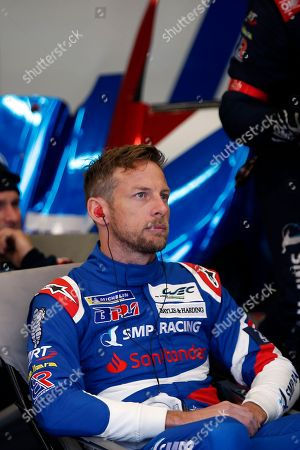 Britain's driver Jenson Button waits in stand during the 86th 24-hour Le Mans endurance race, in Le Mans, western France