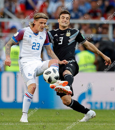 Iceland's Ari Skulason, left, and Argentina's Nicolas Tagliafico fight for the ball during the group D match between Argentina and Iceland at the 2018 soccer World Cup in the Spartak Stadium in Moscow, Russia