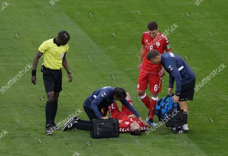 William Kvist, Bakary Gassama. Denmark's William Kvist lies on the pitch as referee Bakary Gassama from Gambia, left, looks on during the group C match between Peru and Denmark at the 2018 soccer World Cup in the Mordovia Arena in Saransk, Russia