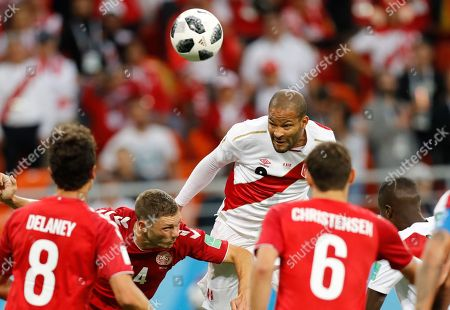 Peru's Alberto Rodriguez, centre, and Denmark's Simon Kjaer, second left, jump for a ball during the group C match between Peru and Denmark at the 2018 soccer World Cup in the Mordovia Arena in Saransk, Russia