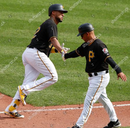 Elias Diaz, Joey Cora. Pittsburgh Pirates' Elias Diaz, left, rounds third to greetings from coach Joey Cora after hitting a solo home run off Cincinnati Reds starting pitcher Luis Castillo in the fourth inning of a baseball game in Pittsburgh