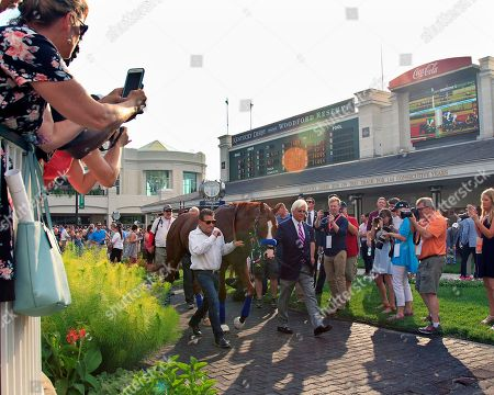 Trainer Bob Baffert, right, and assistant Jimmy Barnes, left, lead Triple Crown winner Justify around the paddock at Churchill Downs, in Louisville, Ky. The colt was paraded before the fans at the track before the third race of the night