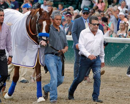 Triple Crown winner Justify is brought over to the paddock at Churchill Downs, in Louisville, Ky. Assistant trainer Jimmy Barnes, right, and groom Eduardo Luna lead the colt