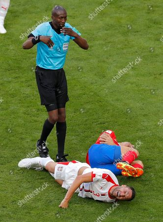 Referee Malang Diedhiou of Senegal stands near Serbia's Dusko Tosic, bottom, and Costa Rica's Johnny Acosta, lieing on the pitch after colliding, during the group E match between Costa Rica and Serbia at the 2018 soccer World Cup in the Samara Arena in Samara, Russia