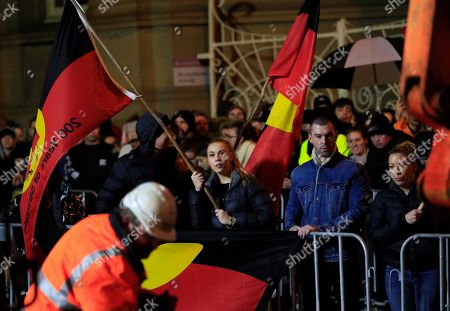 Spectators carry Aboriginal flags as they watch the excavation of artist Mike Parr after being encased for three days beneath Macquarie St during Tasmania's Dark Mofo festival in Hobart, Australia, 17 June 2018. The performance is called 'Underneath The Bitumen The Artist'.