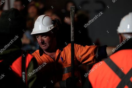 A worker helps excavate artist Mike Parr after being encased for three days beneath Macquarie St during Tasmania's Dark Mofo festival in Hobart, Australia, 17 June 2018.The performance is called 'Underneath The Bitumen The Artist'.