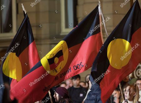 Spectators carry Aboriginal flags as they watch the excavation of artist Mike Parr after being encased for three days beneath Macquarie St during Tasmania's Dark Mofo festival in Hobart, Australia, 17 June 2018.The performance is called 'Underneath The Bitumen The Artist'.
