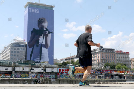 """A man passes a 63 meter high image from the Austrian artist Gottfried Helnwein with the title """" I saw this"""" in Vienna, Austria"""