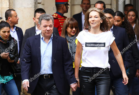 Colombia's President Juan Manuel Santos, lefts, arrives with his wife Maria Clemencia Rodriguez to vote in a presidential runoff election in Bogota, Colombia, . Voters will choose between Ivan Duque, a young conservative lawmaker, and Gustavo Petro, a leftist former guerrilla and ex-Bogota mayor